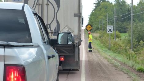 Kanadische Straßenbaustelle: Vorn und hinten je einer, der ein Stop / Slow - Schild hält und dann dreht, wenn man weiter darf. Langsam!